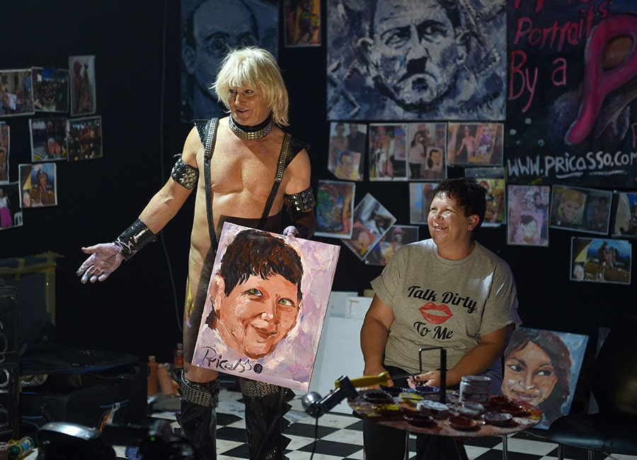 Pricasso showing the audience a portrait he completed during a live painting show